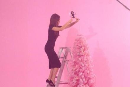 Victoria Beckham wearing heels to decorate her Christmas tree